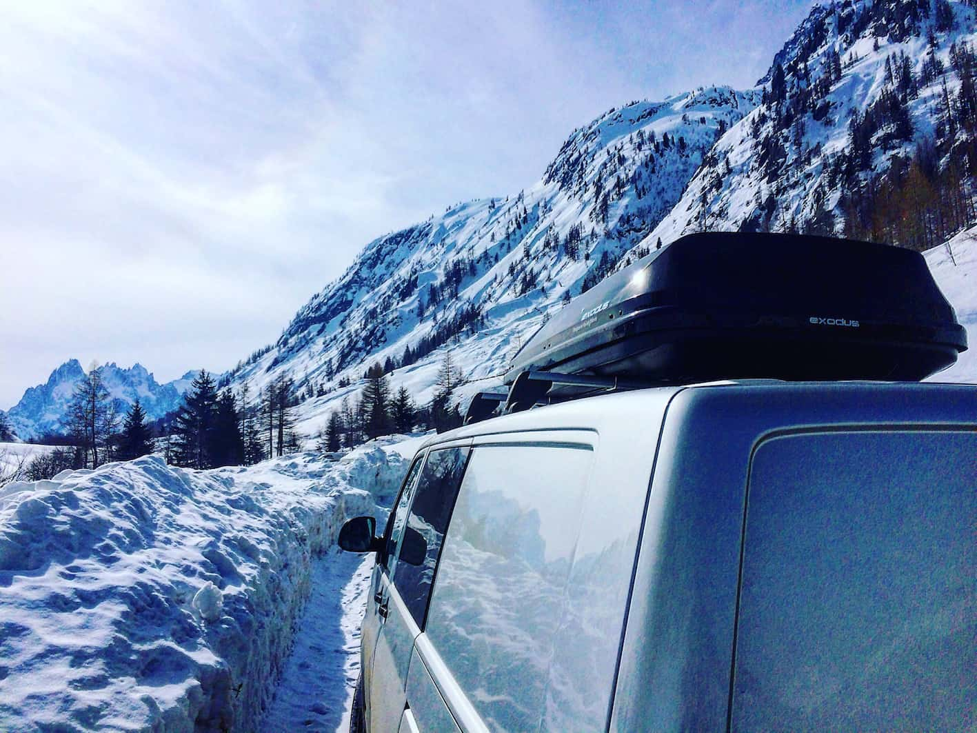 van with roof box in snowy mountain scene